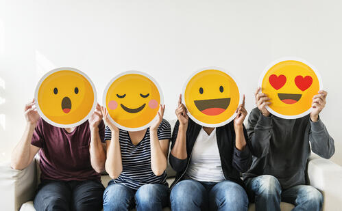4 people holding emoji masks with excited and happy reactions
